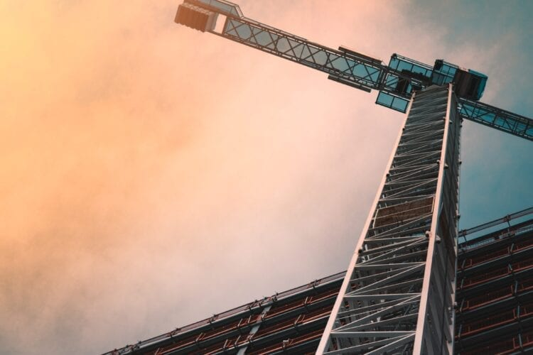 low angle photography of gray tower crane
