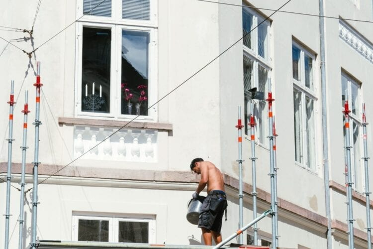 man in black t-shirt and black shorts sitting on black metal railings during daytime