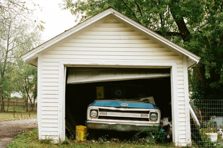 blue chevrolet car parked beside white wooden house